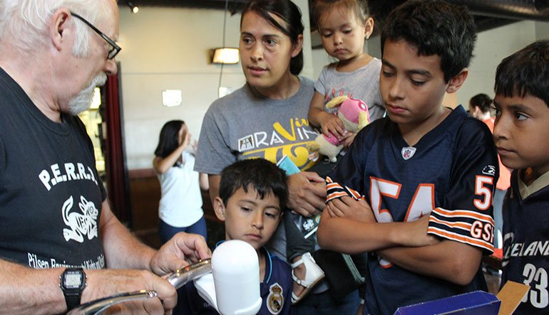 Jack Ailey of PERRO shows Maria Arriaga and her children how to install a faucet-mounted water filter.