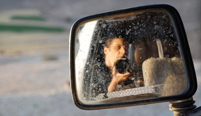 Man with camera in rear-view mirror.