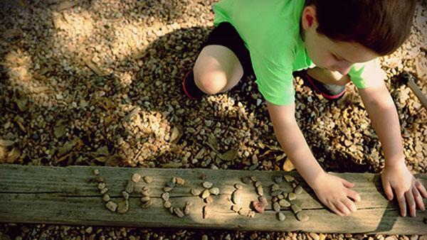 Boy spelling with stones