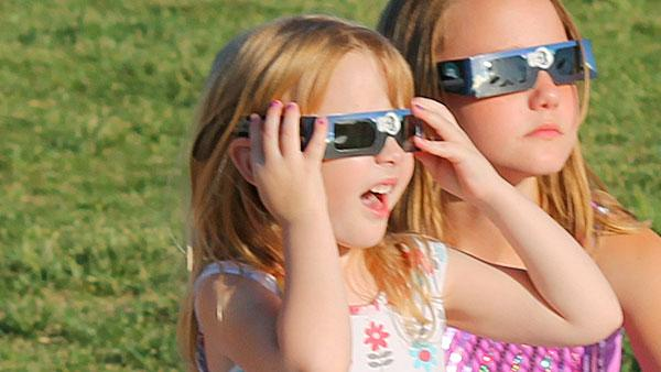 Girls wearing eclipse glasses.