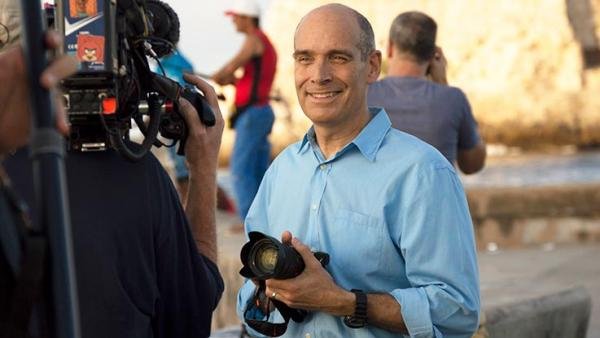 Geoffrey Baer standing in front of a camera