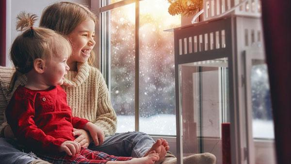 Little girl and boy looking at the snow outside.