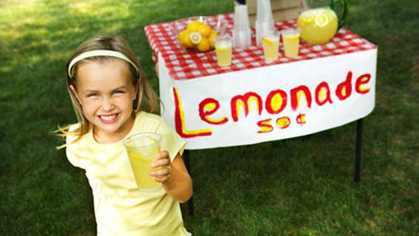Little girl standing by her lemonade stand