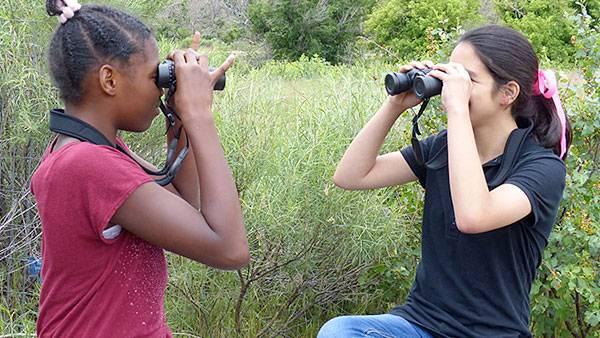 Two girls with binoculars.