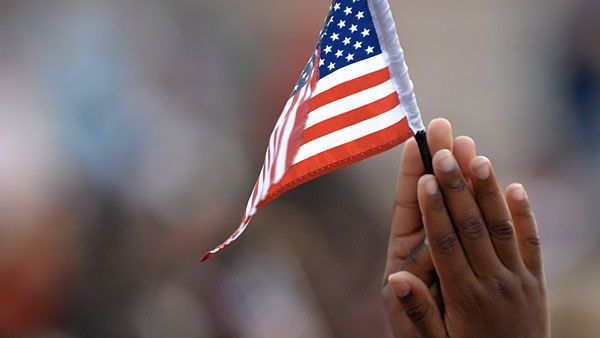 Child's hands holding small American flag.