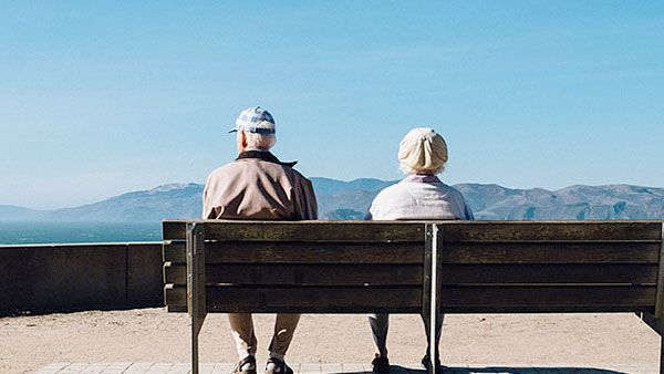 An older couple on a bench near mountains.
