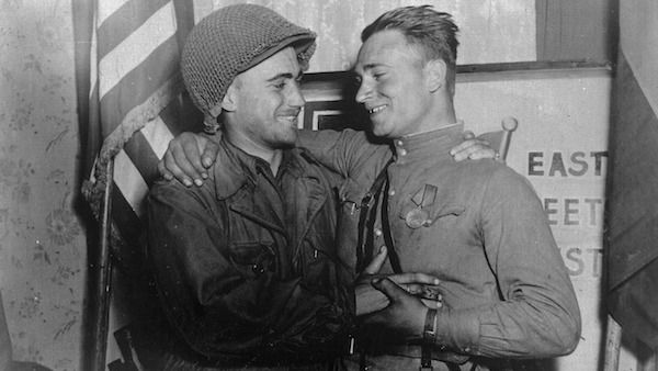 2nd Lt. William Robertson and Lt. Alexander Sylvashko, Red Army, shown in front of a sign symbolizing the historic meeting of the Soviet and American Armies, near Torgau, Germany on Elbe Day. Photo: Pfc. William E. Poulson/U.S. National Archives and Records Administration