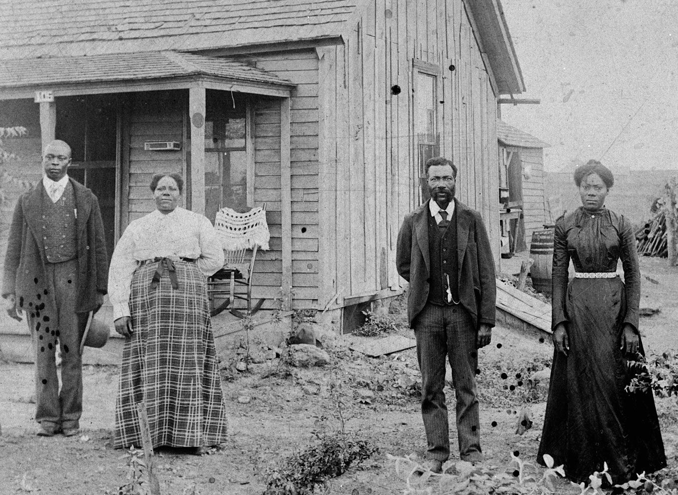 Early African American homesteading family, standing outside home in Nicodemus Historic District, Kansas.