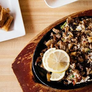 Sisig, a widely loved drinking food consisting of parts of a pig head served in a sizzling-hot cast iron dish with egg mixed in, from Lincoln Square's Isla Pilipina. Photo: Sandy Noto for WTTW
