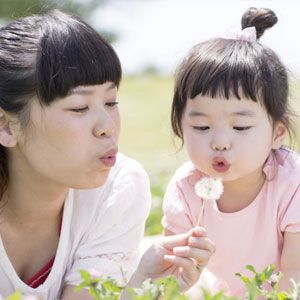 Mom and daughter with dandelion.